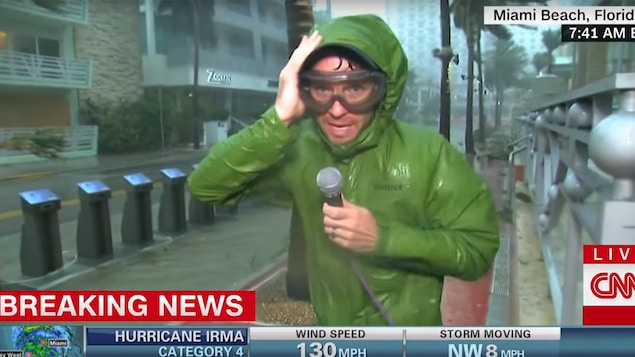Un journaliste parle à la caméra en tenant son capuchon, à la pluie battante, durant l'ouragan Irma de 2017.