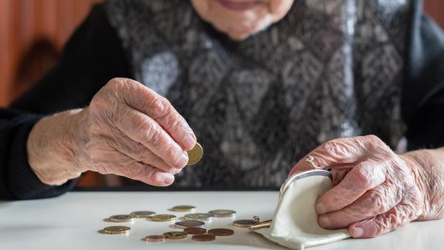 Un dame âgée conte ses sous, posés sur une table devant elle.