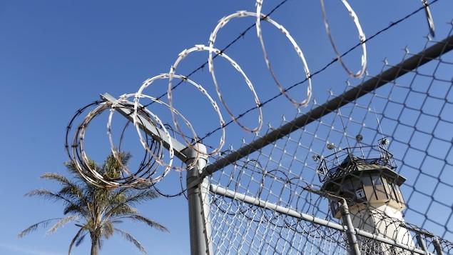Une clôture surmontée de fil barbelé autour d'une prison, en Californie.