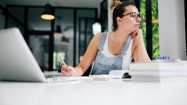 Une jeune femme regarde au loin pendant qu'elle étudie.