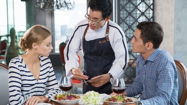 Un serveur et des clients au restaurant