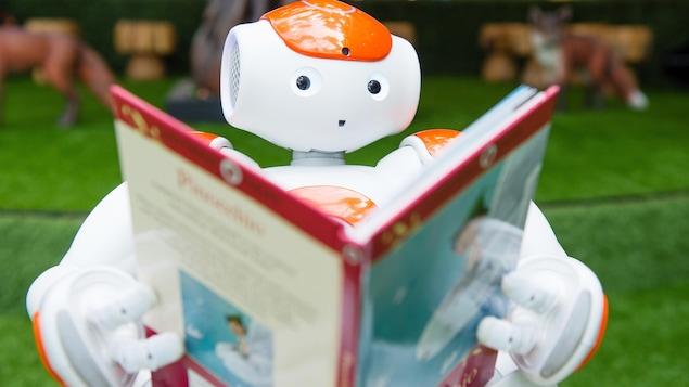 Un robot à l'allure sympathique tient un livre et fait mine de lire.