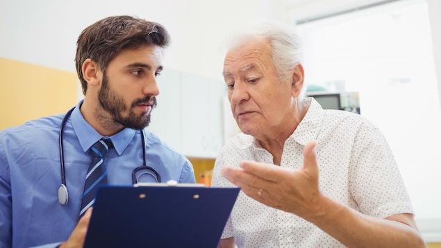 Un homme âgé discute avec son jeune médecin.