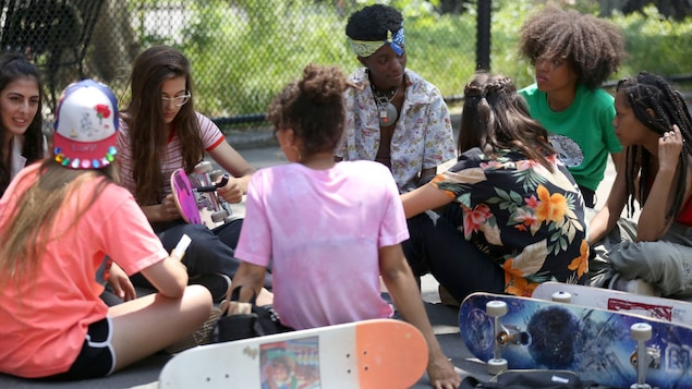 De jeunes planchistes sont assises dans un parc, à New York.