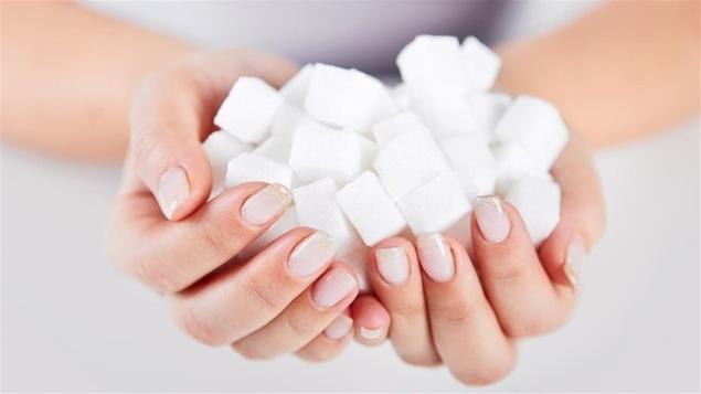 Une femme tient des cubes de sucre dans ses mains.