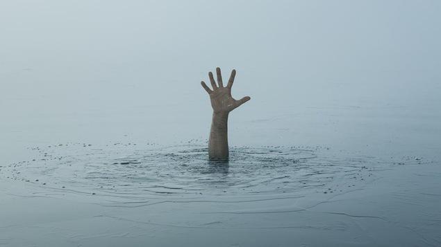 Une main émergeant d'un plan d'eau illustre la problématique du suicide.