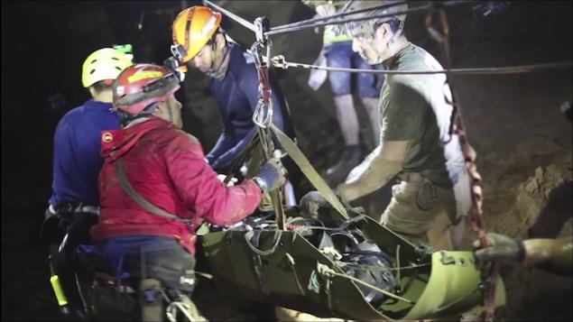 Des sauveteurs en train de secourir les douze jeunes joueurs de soccer et leur entraîneur dans la grotte Tham Luang Nang Non à Mae Sai, dans la province de Chiang Rai, en Thaïlande, le 11 juillet.