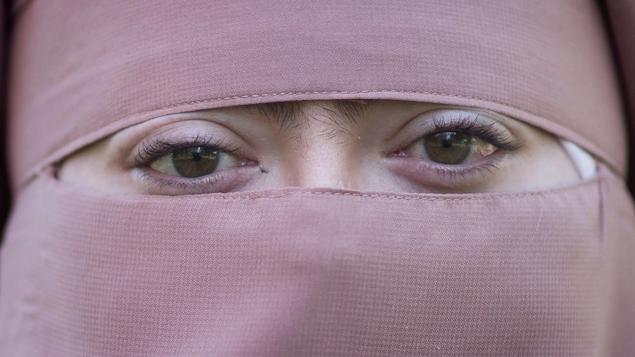 Une femme en niqab rose, vue en gros plan, regarde droit dans la caméra.