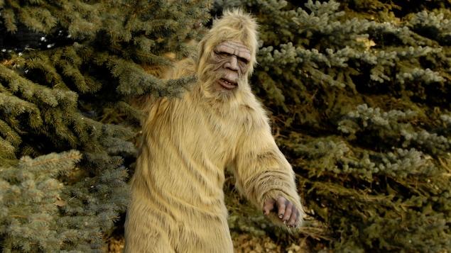 Un homme costumé en yéti, en sasquatch ou en abominable homme des neiges, partiellement dissimulé derrière un arbre