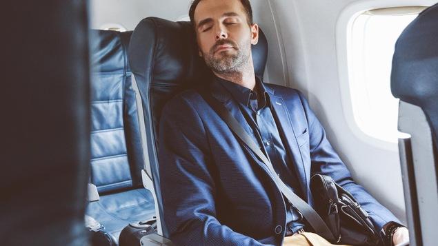 Un homme d'affaires dort dans un avion.
