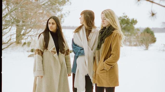 Les trois femmes debouts dans la neige en campagne.