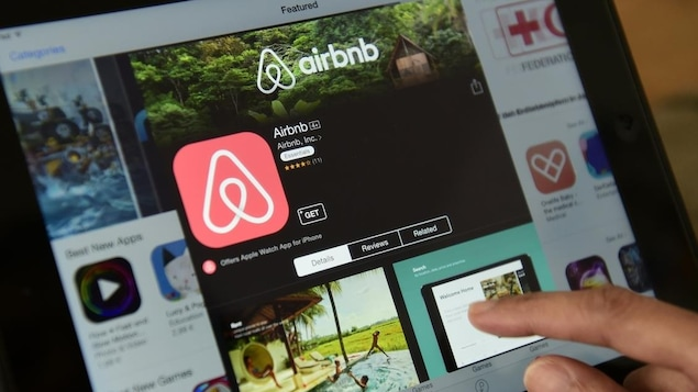 Un aperçu de l'application Airbnb sur une tablette où on voit le logo et une photo de piscine.