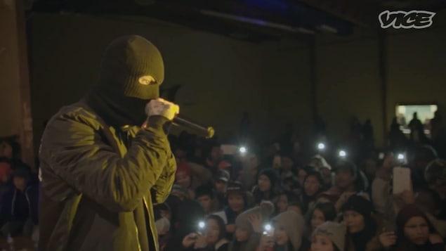 Souldia chante avec un masque devant une foule de jeunes Autochtones.