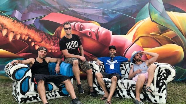 Quatre membres du ASHOP CREW assis sur des divans devant leur murale aux Wynwood Walls à Miami.