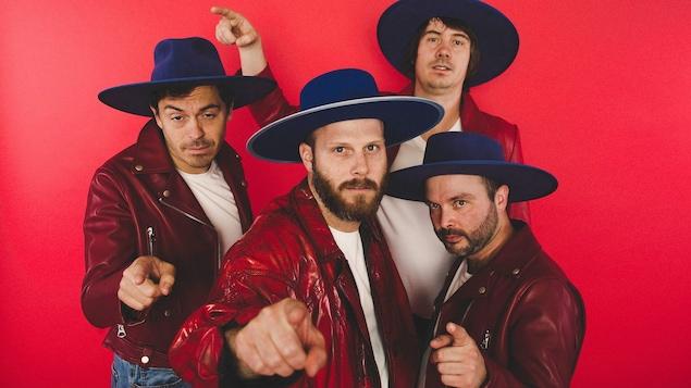 Sur fond rouge, les quatre membre de Bleu Jeans Bleu avec une veste de cuir rouge foncée et un chapeau bleu à larges bords.