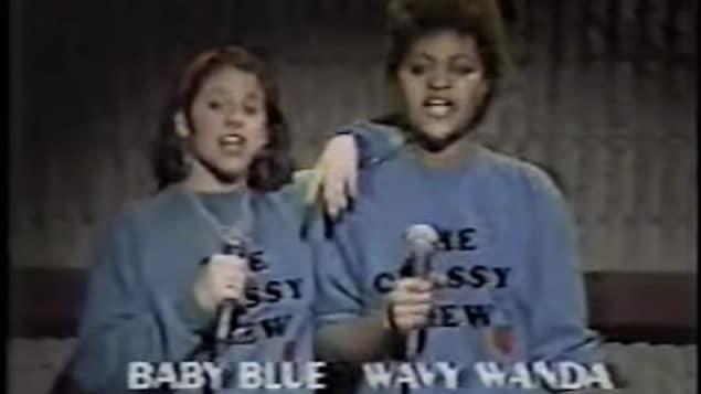 Capture d'écran un peu brouillée de Baby Blue et Wavy Wanda avec un chandail coton ouaté portant l'inscription «Classy Crew». Elles tiennent un micro et son en train de rapper.