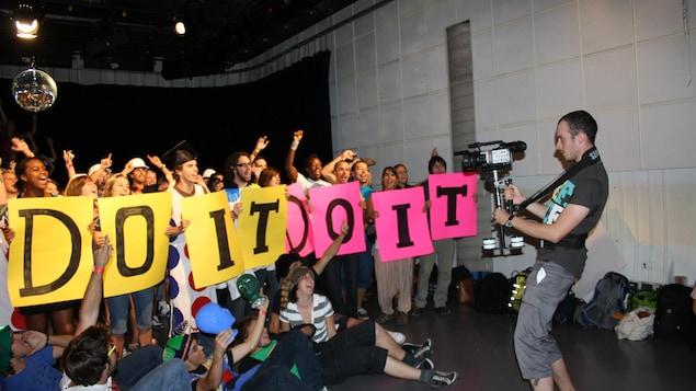 Une foule qui tient des pancartes « do it » est filmée par un caméraman.