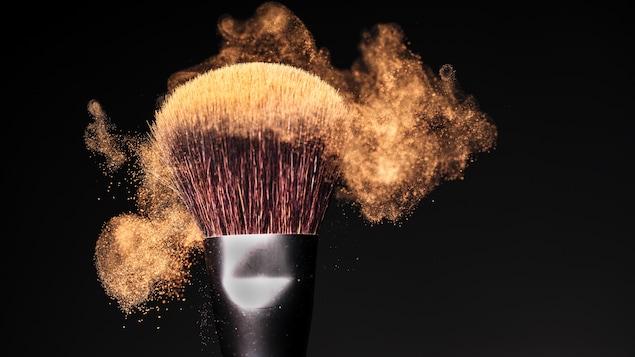 Un pinceau à maquillage avec de la poudre brillante, sur fond noir.