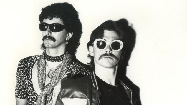 Photo en noir et blanc des deux hommes avec des lunettes soleil extravagantes et des moustaches.