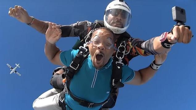 Will Smith en chute libre, avec un accompagnateur et un parachute sur le dos.