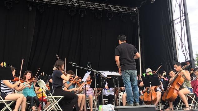 L'Orchestre des jeunes du Nouveau-Brunswick en répétition sur la scène du Parc Riverain à Moncton en prévision de l'événement POPs NB.