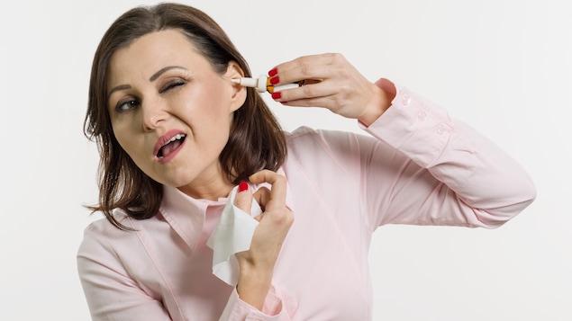 Une femme tente, sans succès, de mettre des gouttes dans son oreille.