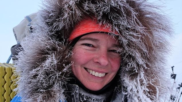 Une femme porte un manteau d'hiver dont le bord du capuchon est complètement givré.