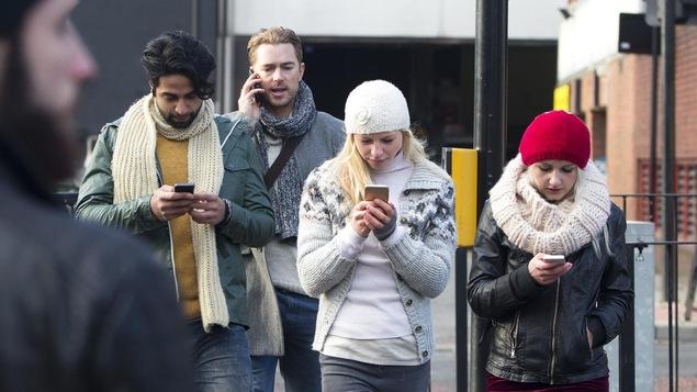Trois d'entre eux regardent leur cellulaire tout en marchant, tandis qu'un autre parle au téléphone.