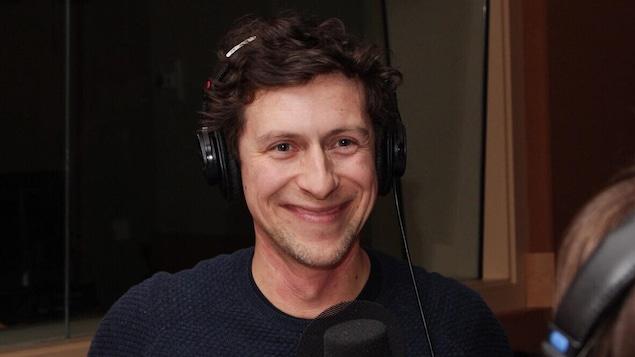 Un homme est devant un micro où il répond à des questions dans un studio de radio.