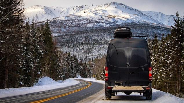 On voit un véhicule fourgonnette sur une route, immobile. Devant, il y a des montagnes enneigées.