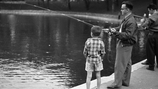 Photo en noir et blanc montrant un homme et un enfant en train de pêcher au bord d'un bassin.