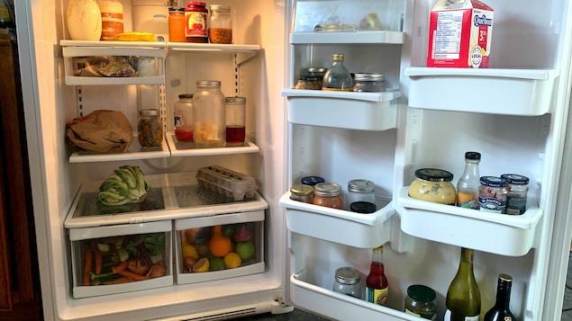 L'intérieur d'un frigo ouvert qui contient des fruits, des légumes et des contenants en verre.
