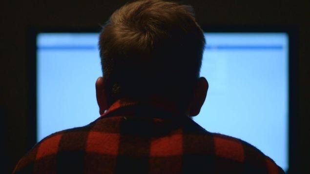 Photo d'un homme de dos qui regarde un écran d'ordinateur.
