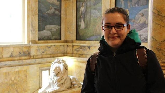 Pénélope Doucet dans la bibliothèque de Boston (près d'une statue de lion en plâtre et des fresques sur les murs)