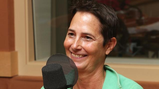 Photo d'Hélène Cyr devant un micro de radio.