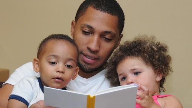 Un père immigrant fait la lecture à ses deux enfants. Le rôle de père est différent d'une culture à l'autre.