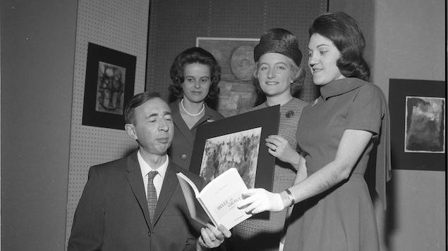 Une photo en noir et blanc où l'on voit trois femmes debout et un homme assis qui regarde un livre.