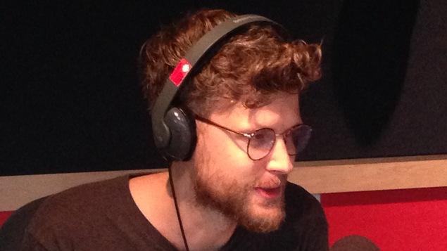 Un homme est assis dans un studio de radio devant un micro où il fait une entrevue