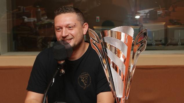 Un homme parle devant un micro dans un studio de radio, en compagnie d'un immense trophée qui rappelle la forme d'une pizza.