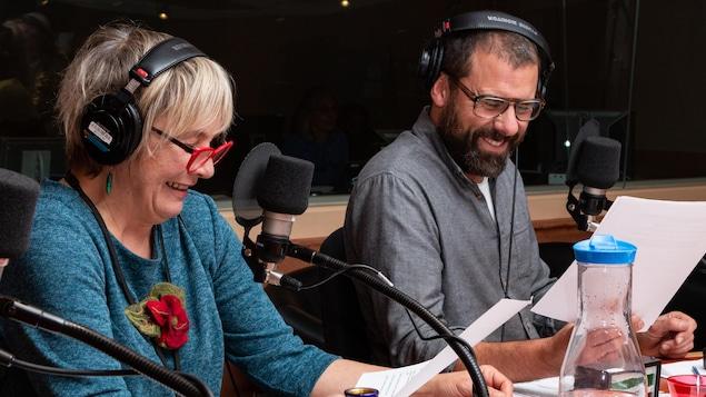 Les deux comédiens sourient en lisant leur feuille.