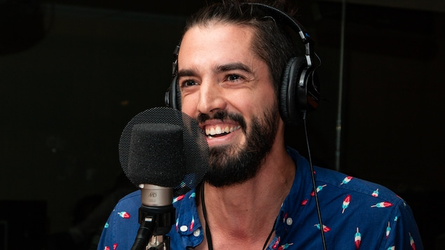 L'artiste barbu sourit à pleines dents au micro de l'émission.