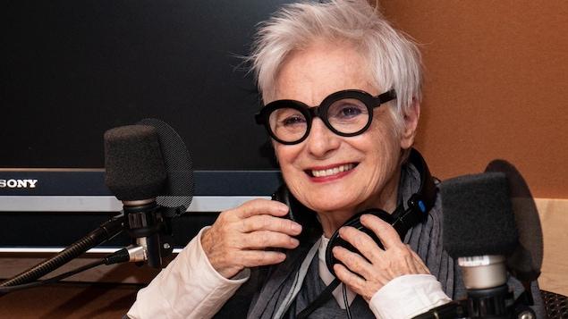 La comédienne à la chevelure argentée sourit à l'animateur.
