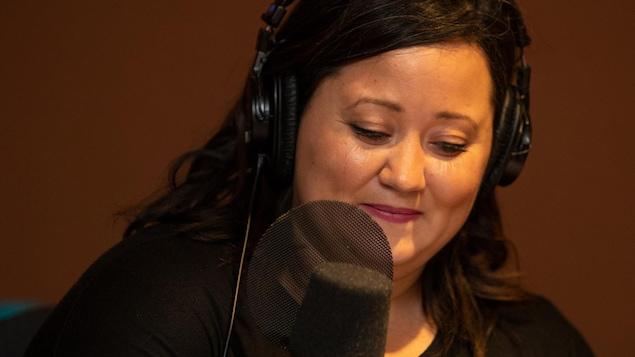 Une femme avec des écouteurs sur la tête est devant un micro.