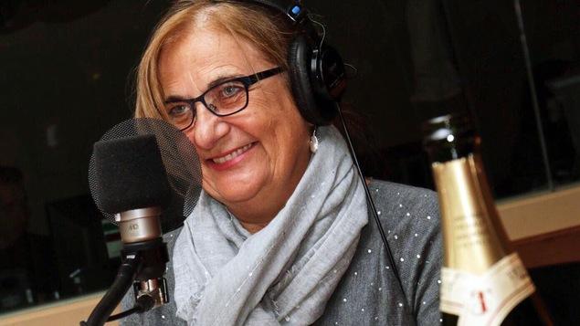 Une femme sourit devant une micro dans un studio de radio. Une bouteille de champagne se trouve en avant-plan.