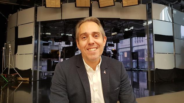 Damien Hubert est assis dans les marches devant le studio télé de CBC/Radio-Canada