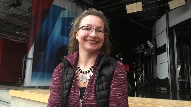 Jocelyne Devisser sourit devant de l'équipement d'éclairage près des plateaux télé de CBC.
