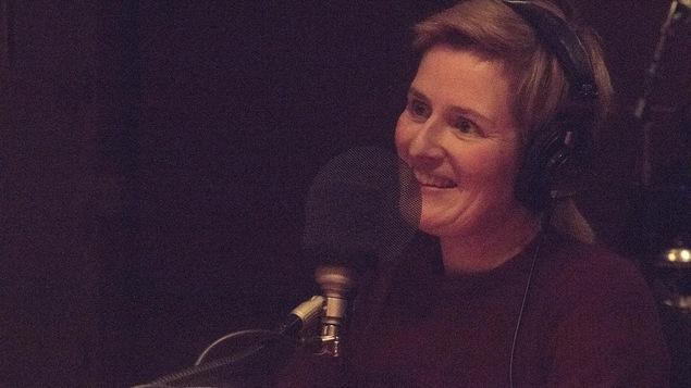La comédienne et autrice Anne-Marie Olivier sourit devant un micro.