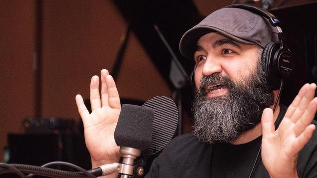 Un homme barbu parle devant un micro, les mains levées.