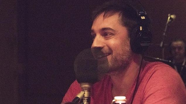 Le comédien et dramaturge Jean-François Nadeau sourit devant un micro.