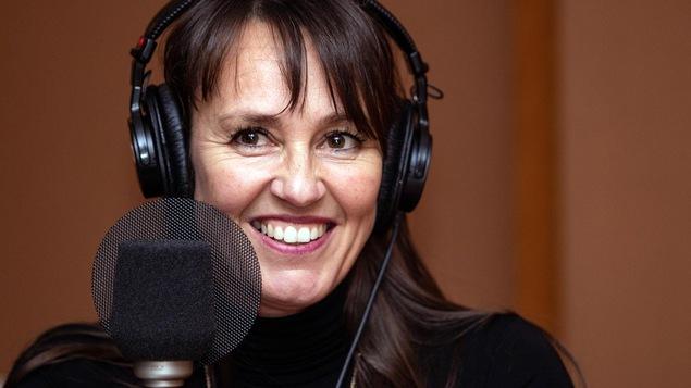 Une femme sourit devant un micro.